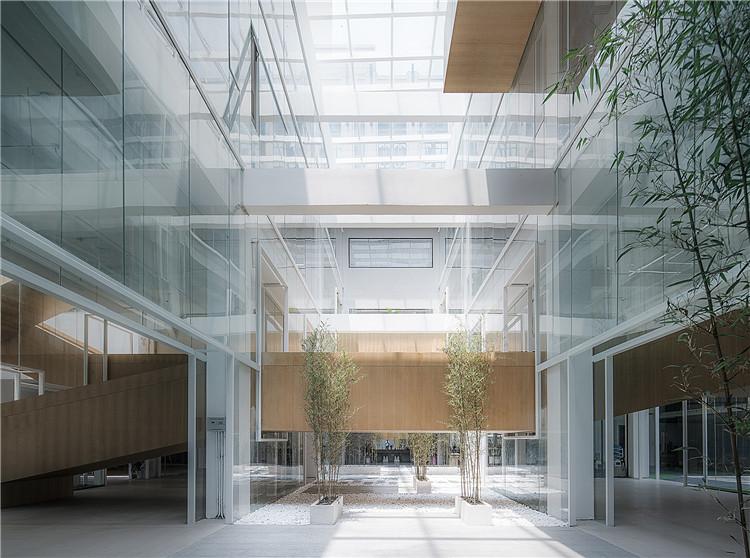 这个空间序列的进一步实现,是靠一个贯穿了整个厂房每一层空间的坡道、连廊与楼梯的体系来完成的,就像一个神经中枢穿越时空:它时而进入通高的中庭,时而进入狭小半私密的开敞空间,同时又连接着楼层之间的流线转换。这个建筑漫步式的体系不仅是交通的内核,更创造了一个丰富而富有身体节奏感的漫步秩序。